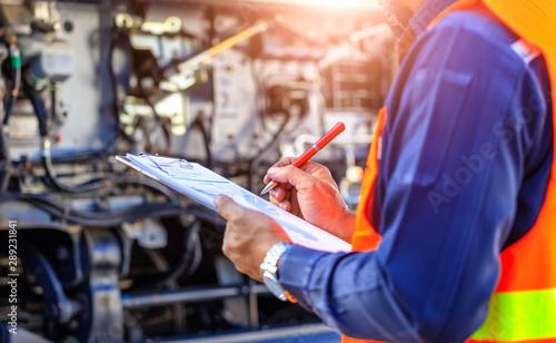 Fotografia Preforming a pre-trip inspection on a truck,Concept preventive maintenance truck checklist,Check truck engine,Check the lubricating oil,spot focus