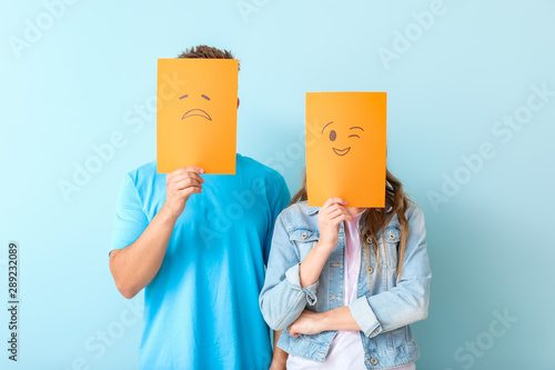 Fototapeta  Young couple hiding faces behind emoticons against color background