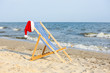 Beach chair with Santa Claus hat on sea coast. Christmas vacation
