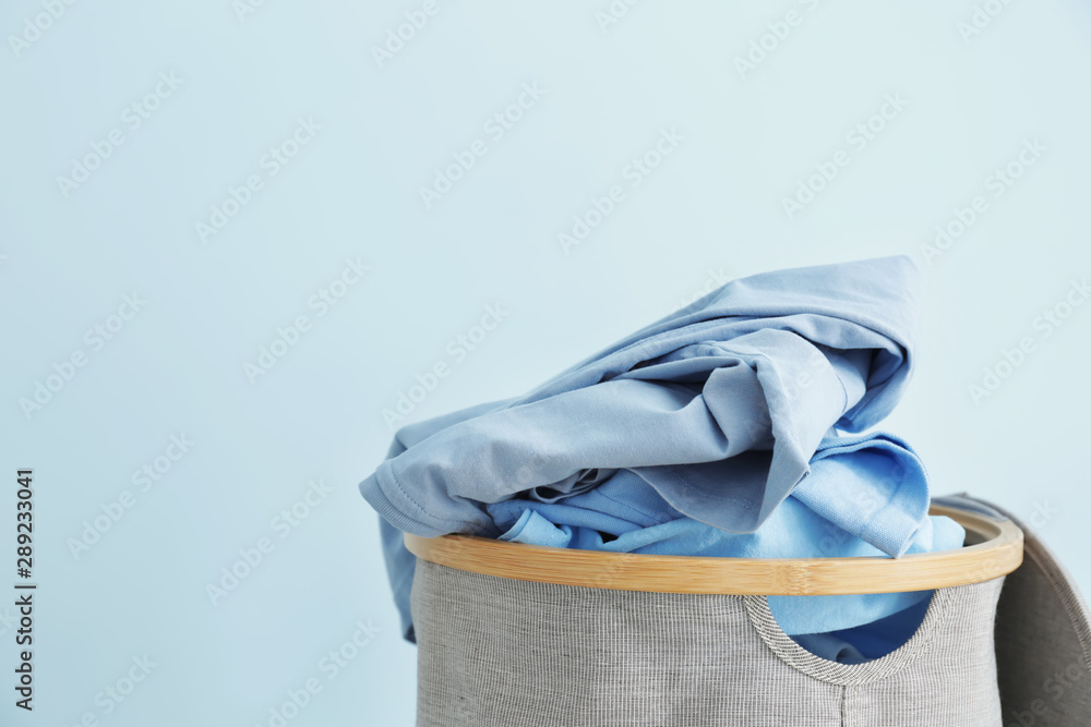 Fototapeta Basket with dirty laundry on color background