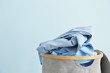 canvas print picture - Basket with dirty laundry on color background