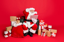 Full Body Photo Of Impressed Santa Claus In Hat With Eyewear Eyeglasses Read Noel News On His Laptop Feel Stupor Isolated Over Red Background