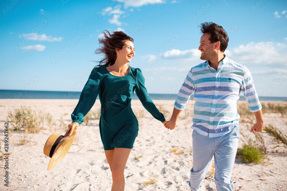 Fototapeta Couple walking on beach. Young happy interracial couple walking on beach smiling holding around each other. Asian woman, Caucasian man.