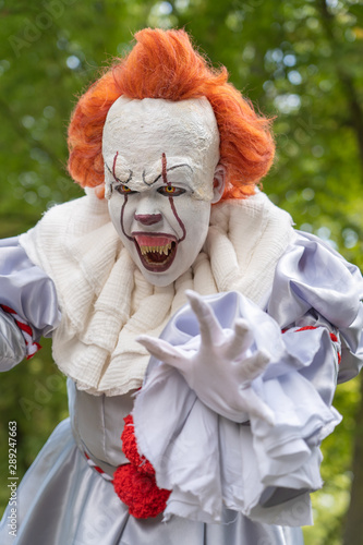 Dangerous horror clown reaches for a victim with his hands