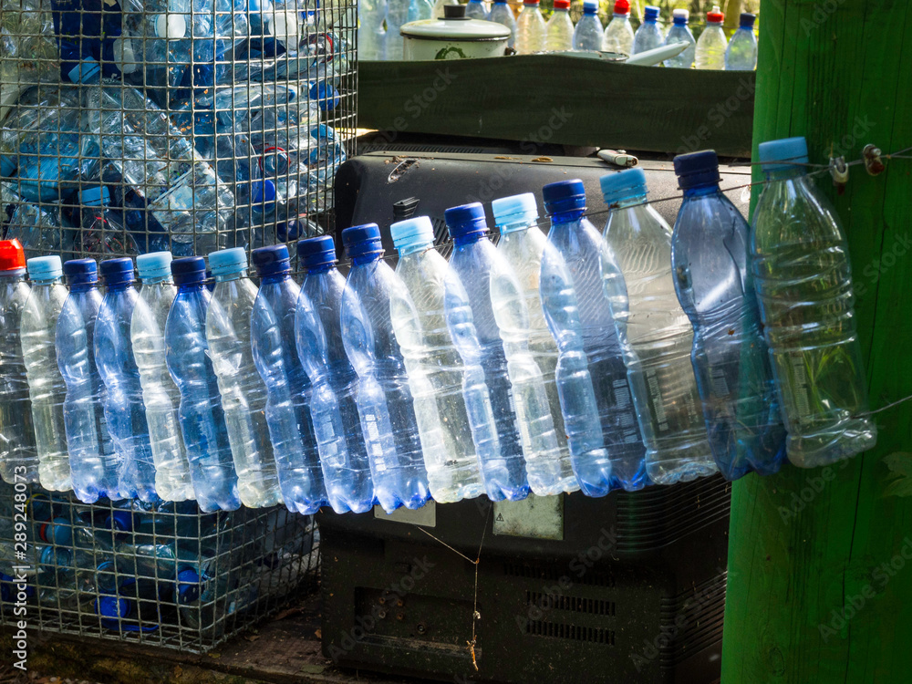 Fototapeta empty used plastic bottles on green forest, recycling concept