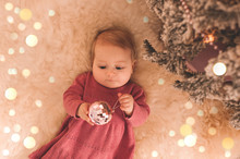 Pretty Baby Girl 1 Year Old Holding Christmas Ball Wearing Knitted Dress Lying Under Christmas Tree Over Lights Closeup. Merry Christmas. Ney Year. Childhood.