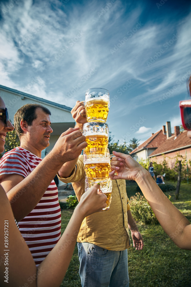 Fototapety, obrazy: Group of young people enjoying and cheering beer outdoors.