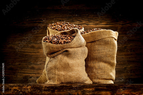 Fresh coffee in sack and wooden wall background
