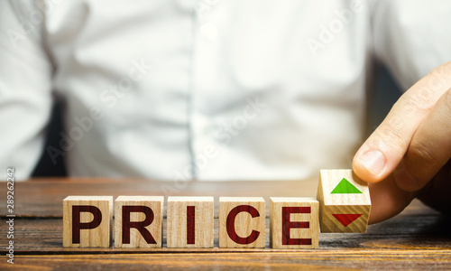 Vászonkép  A man changes the position of a block with symbols of growth and decline near the word Price