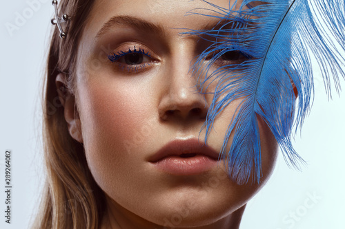 Fotografie, Tablou  Beautiful tanned girl with creative make-up and blue eyelashes, feather in hand