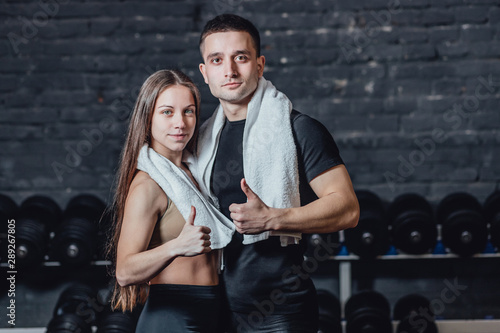 Fototapeta Young sporty couple guy and girl standing in gym. During this, the white scumbag is held on the neck. Standing on a black background and looking at the camera. obraz na płótnie