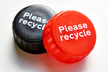 Black And Red Bottle Cap With Please Recycle Message Against A White Background. Concept Of Plastic Pollution.