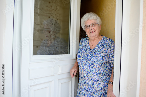 elderly senior woman opening front door of house and welcoming people at home Canvas Print