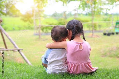 Fototapeta Older sister hugs little brother by the neck, shoulders sitting on green grass field. Two adorable Asian children sitting and hugging the neck rear view. obraz