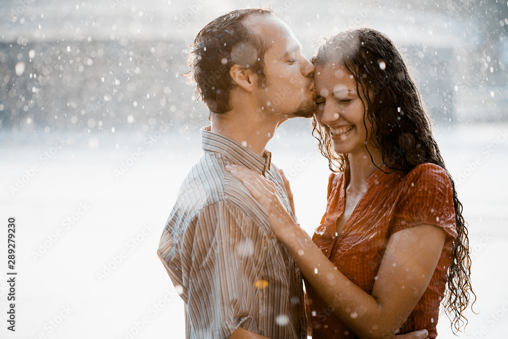 Fototapeta Couple in love hugging and kissing under he rain. They are wet and smiling