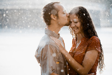 Couple in love hugging and kissing under he rain. They are wet and smiling