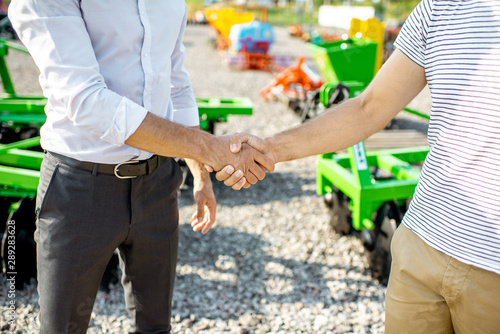 Photo Buyer shaking hand with salesman on the open ground of the agricultural shop, ha