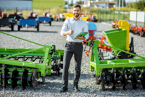 Fototapeta Portrait of a handsome salesman standing near the plow at the outdoor ground of the shop with new agricultural machinery obraz