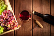 canvas print picture - Cellar Tasting. A photo of a red wine glass with a bottle, grapes, and a vintage corkscew, shot from the top on a dark rustic wooden background