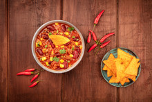 Chili Con Carne, A Traditional Mexican Dish With Red Beans, Cilantro Leaves, Ground Meat, And Chili Peppers, Overhead Shot With Nachos On A Dark Rustic Wooden Background