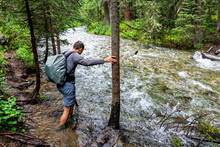 Man Crossing River Ford On Conundrum Creek Trail In Aspen, Colorado In 2019 Summer In Forest Woods With Strong Current