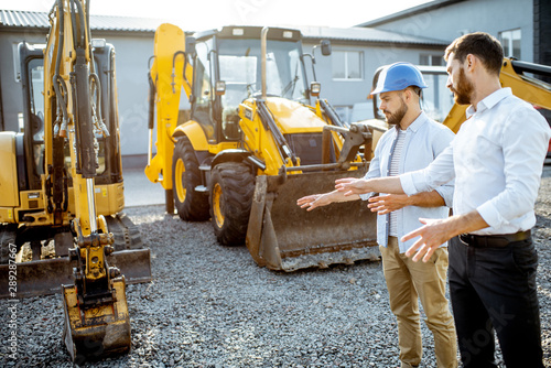 Fotografía Builder choosing heavy machinery for construction with a sales consultant on the