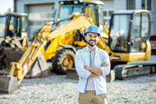 Portrait Of A Handsome Builder Standing On The Open Ground Of The Shop With Heavy Machinery For Construction
