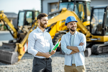 Builder choosing heavy machinery for construction with a sales consultant standing with some documents on the open ground of a shop with special vehicles