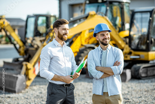 Fotografía Builder choosing heavy machinery for construction with a sales consultant standi