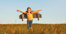 Child Pilot Aviator With Wings Of Airplane Dreams Of Traveling In Summer  At Sunset