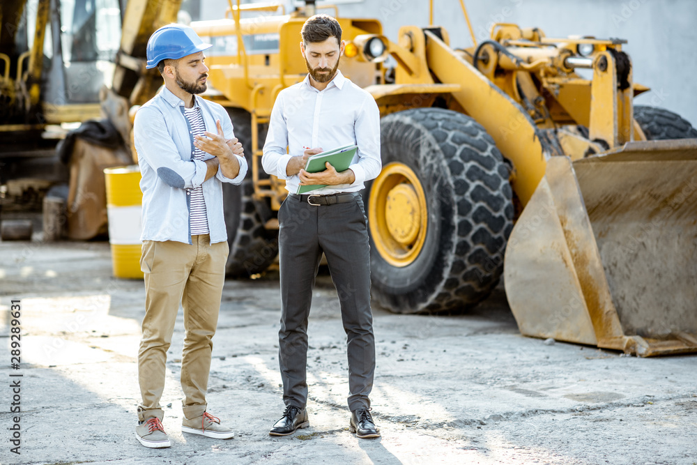Fototapeta Builder choosing heavy machinery for construction with a sales consultant, signing some documents on the open ground of a shop with special vehicles