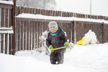 A Little Boy Cleans A Shovel Paths In The Yard From Snow