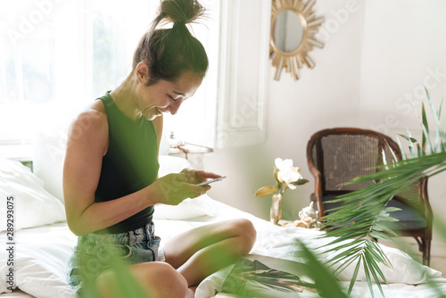Deurstickers Ontspanning Portrait of joyous woman holding cellphone while reading magazine on bed in bright room with green plant