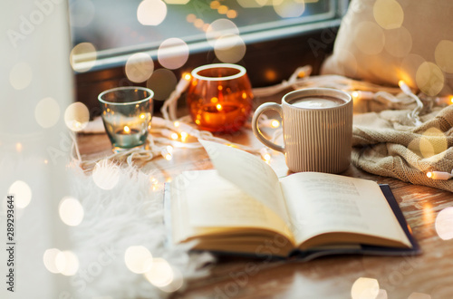 hygge and cozy home concept - book, cup of coffee or hot cchocolate and candles with garland on window sill
