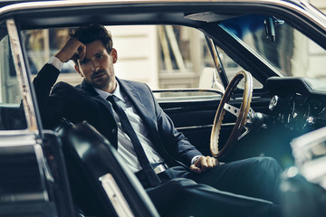 Handsome man in black suit sitting in the old car
