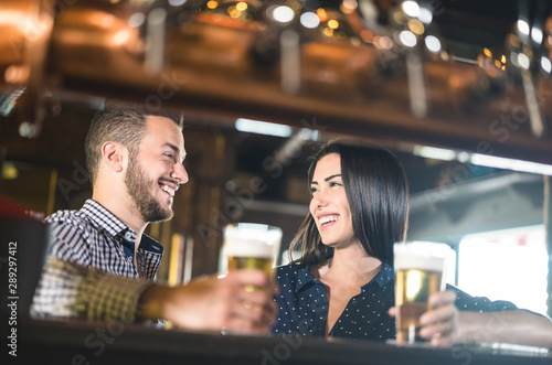 Vászonkép Young couple at beginnings of love story - Pretty woman drinking beer with hands