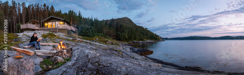 Fotografia panoramic view woman reading near campfire in norway