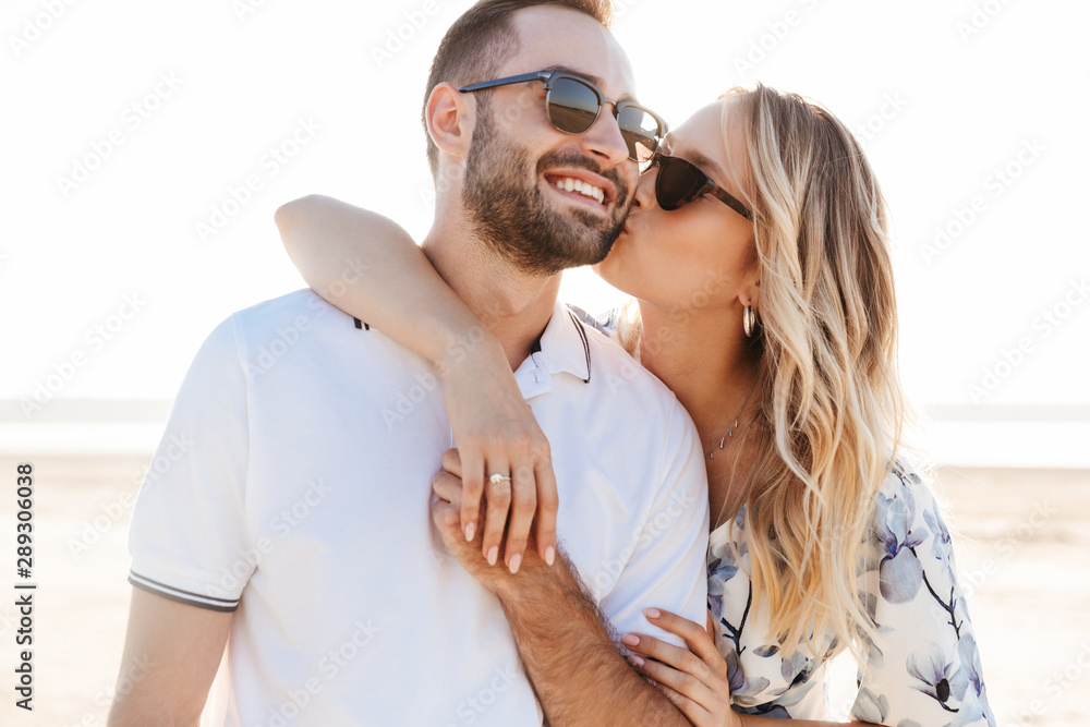 Fototapeta Photo of lovely young woman kissing and hugging handsome man while walking on sunny beach