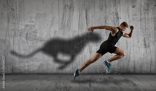 Fotografia Athletic man sprinter running on dark wall background