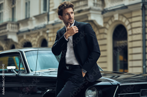 Fotografie, Obraz  Young handsome man with black classic car wearing black suit