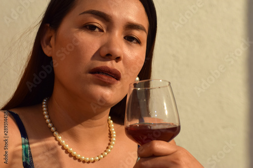 beautiful, drunken middle aged woman holding wine glass close to her lips Canvas-taulu