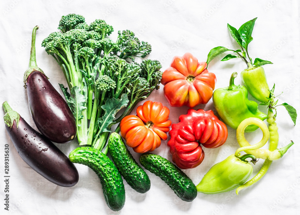 Fototapety, obrazy: Fresh seasonal vegetables food background. Aubergines, tomatoes, peppers, broccoli on a light background, top view. Flat lay, copy space