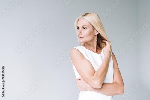 Fototapeta happy blonde elegant mature woman looking away isolated on grey obraz