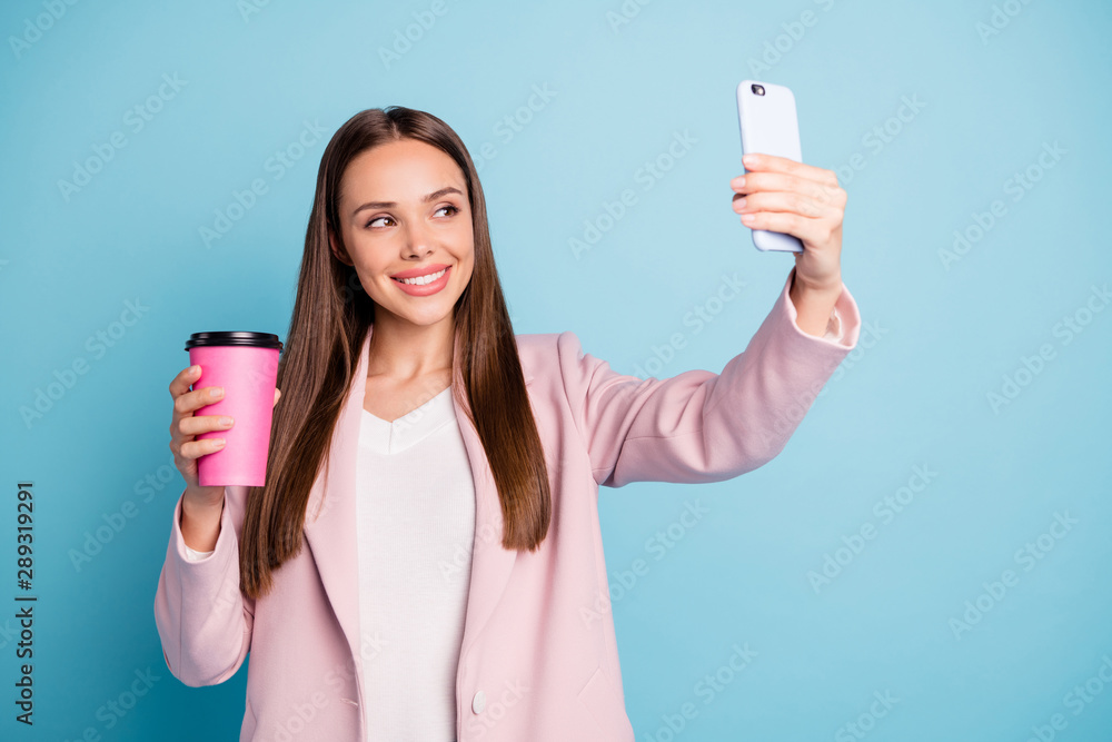 Fototapeta Portrait of cute cheerful lady using her cellphone making selfie holding mug with hot beverage wearing pink coat isolated over blue color background