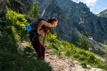 Young Girl Traveler In Red Sportswear With Backpack Leaned On Her Knee And Hold Her Hand On Her Stomach Because Tired Of Climbing A Mountain