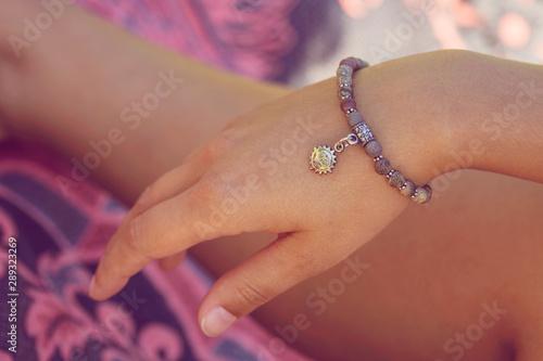 Fotografía  Female hand wearing mineral stone beads yoga bracelet