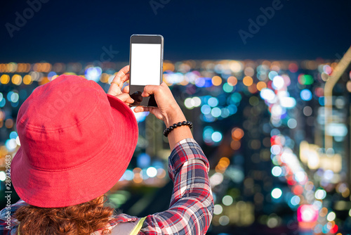 Young female tourists using mobile phones to take pictures bokeh background of Bangkok City skyline with urban skyscrapers at night time Wallpaper Mural