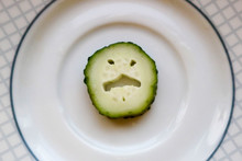 Slice Of Funny Angry Cucumber Face On Plate Background
