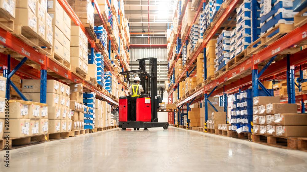 Fototapeta Worker in forklift-truck loading packed goods in huge distribution warehouse with high shelves.