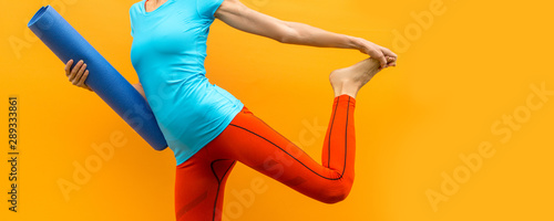 Foto auf AluDibond Yoga schule Sporty yoga girl with yoga mat wearing sport clothes over orange background